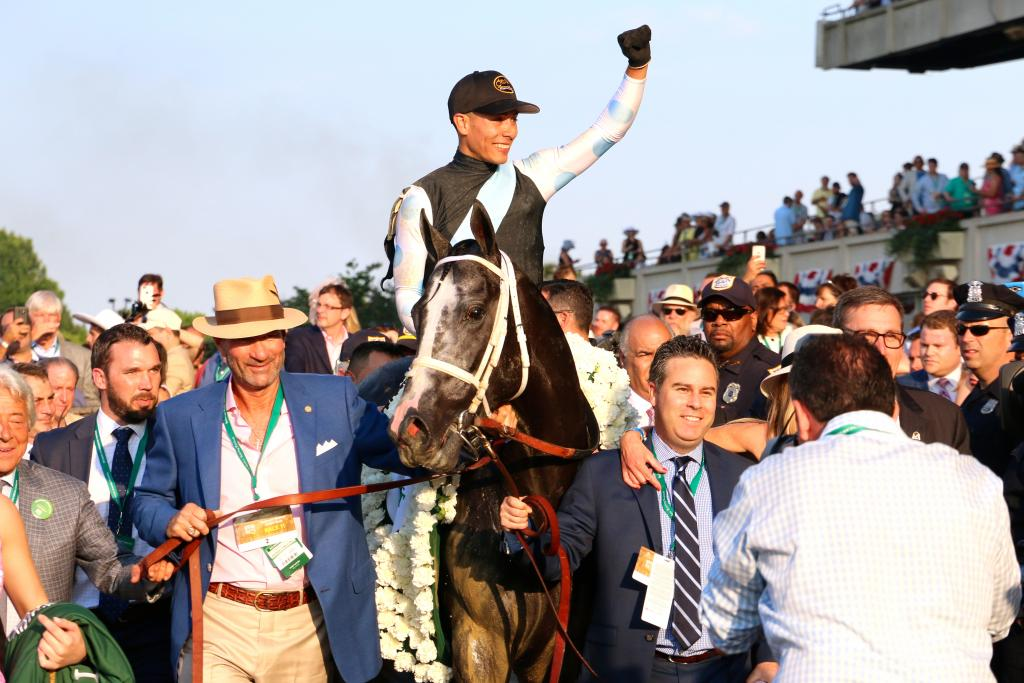 Jockey Jose Ortiz raised a fist in salute to his win aboard Tapwrit as the colt's owners escorted their Belmont Stakes champ down the track's Victory Lane to the winner's circle. (Penelope P. Miller/America's Best Racing)