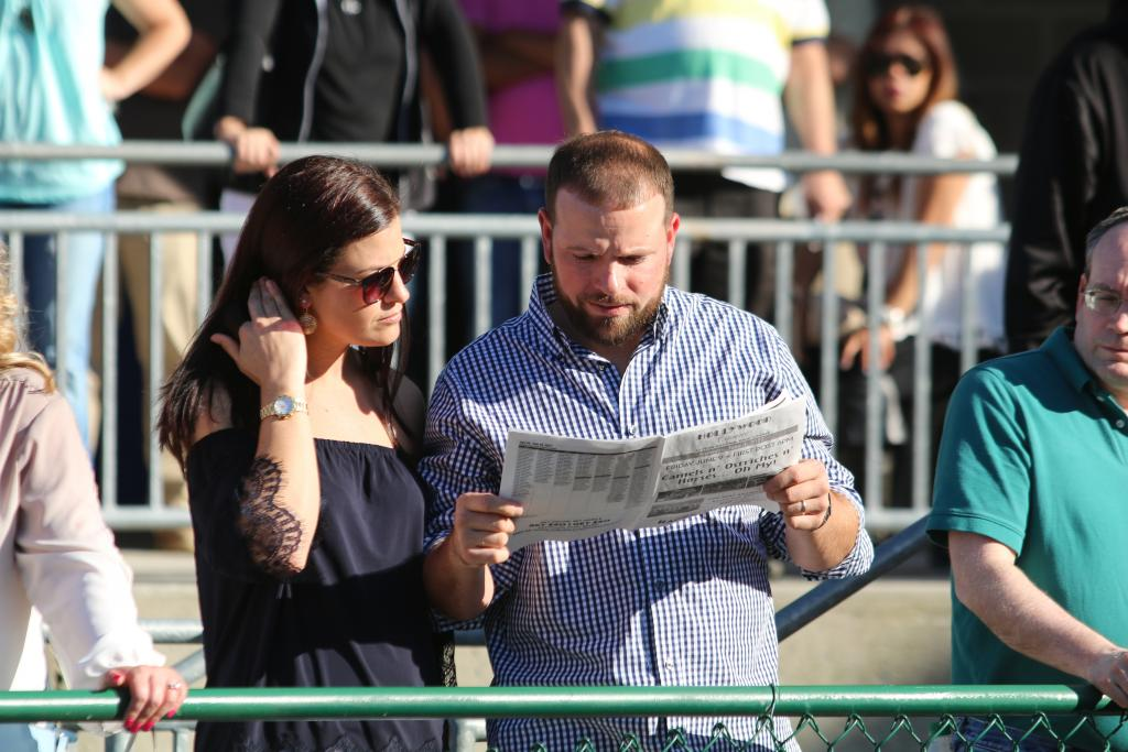 Fans studied their programs, trying to determine the winner of the Penn Mile as the contenders paraded around the paddock before the race. (Penelope P. Miller/America's Best Racing)