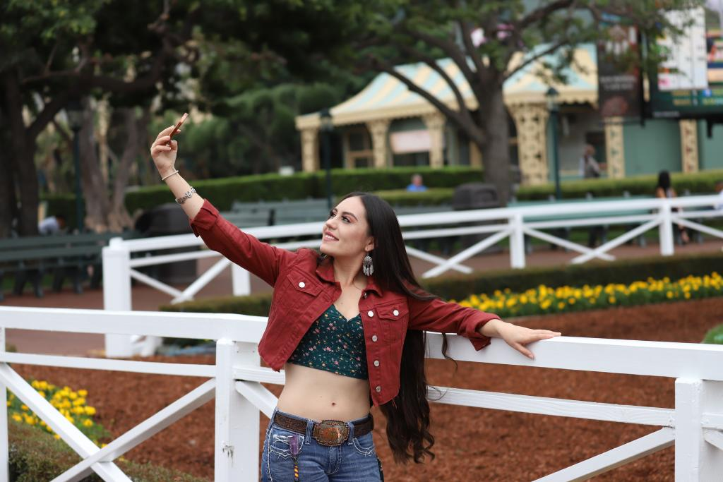 A fan gets the perfect selfie in front of Santa Anita Park's historic paddock. (Penelope P. Miller/America's Best Racing)