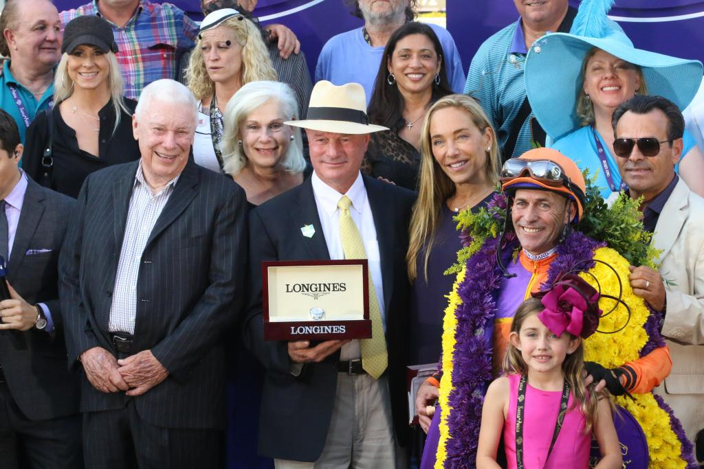 Moments later, Beholder was whisked home as the trophy presentation was made. Beholder's trainer, Richard Mandella, showed off the Longines watch he received for his outstanding accomplishment. (Penelope P. Miller/America's Best Racing)