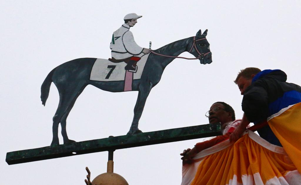 Dr. Lawrence Jones paints the Preakness weathervane. (Julie June Stewart photo)