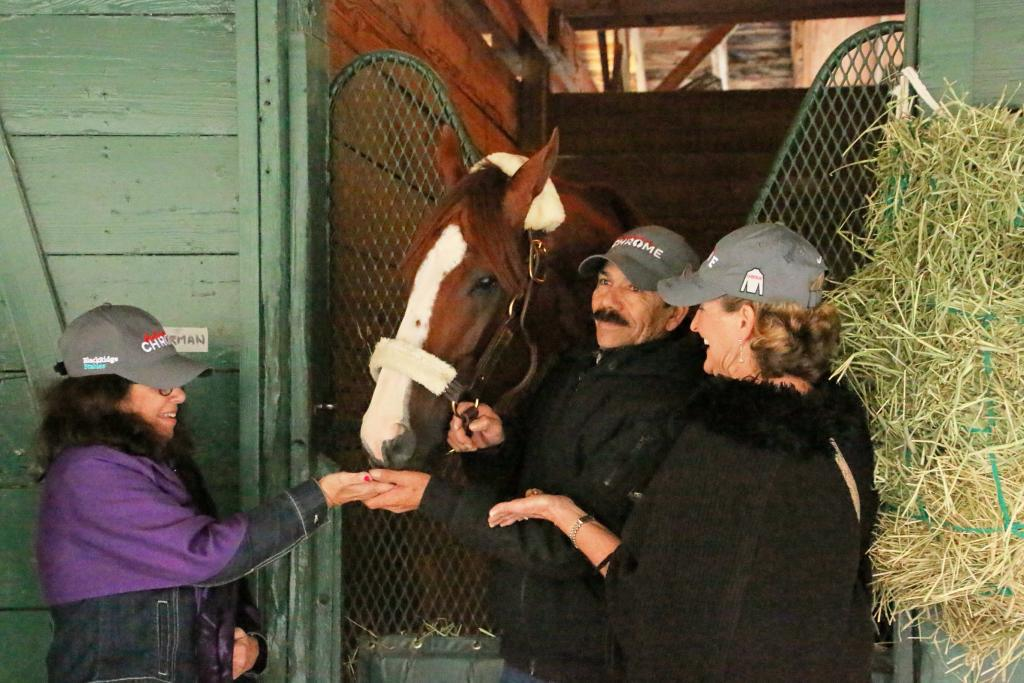Cheryl Hoffman, left, and Zella May Daugherty are taught how to feed California Chrome cookies. (Julie June Stewart photo)