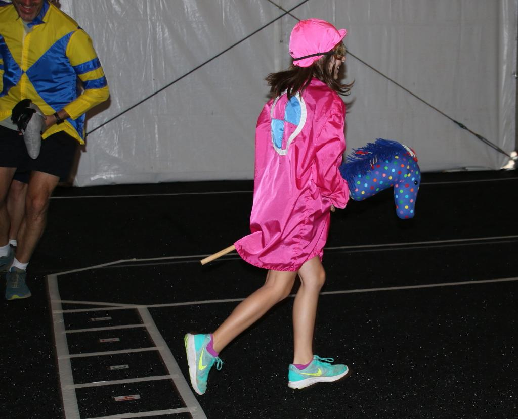 A young fan on her way down the stretch in the stick horse races. (Julie June Stewart photo)