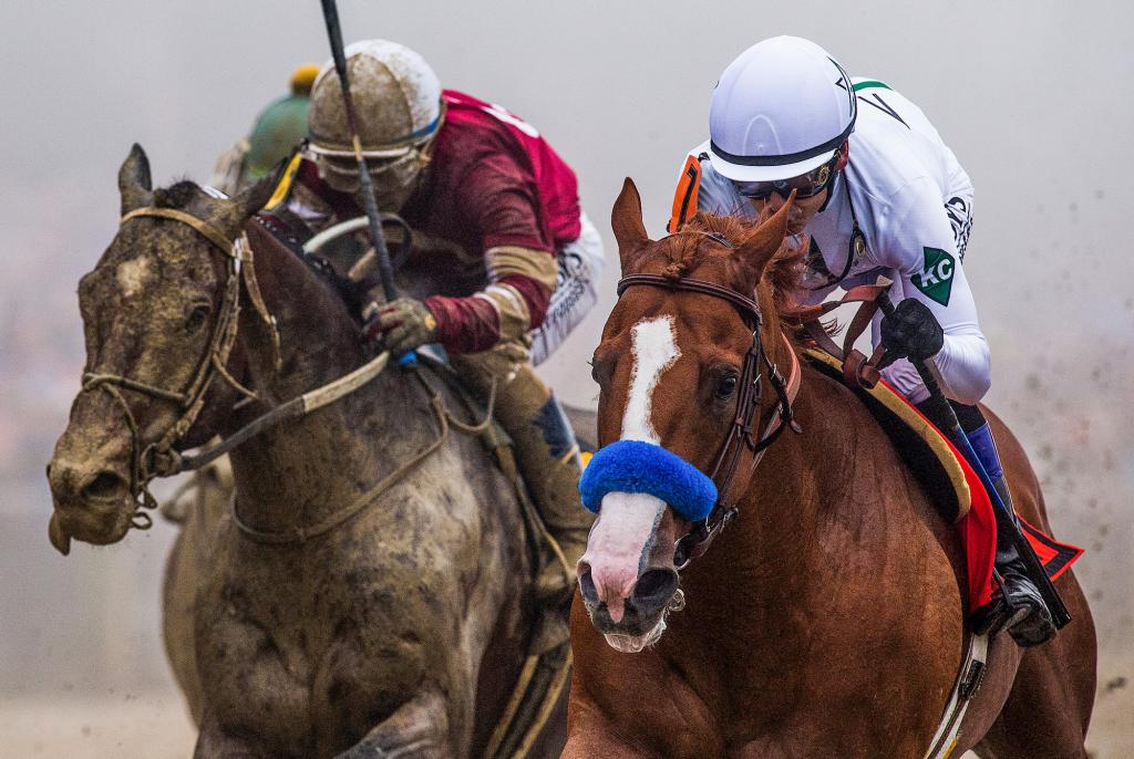 Justify races toward the finish line with third-place finisher Tenfold on his outside flank. (Eclipse Sportswire)