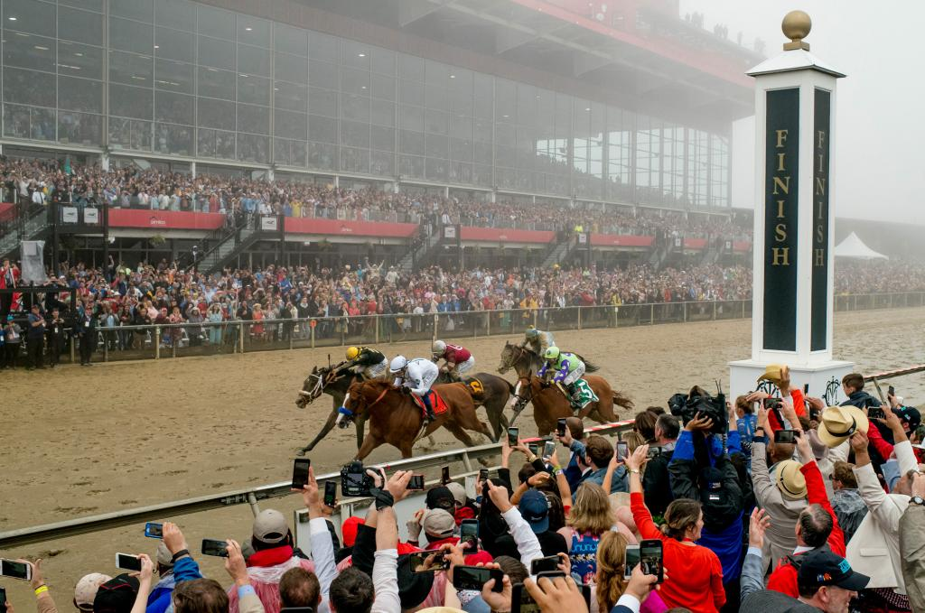 The Pimlico fans cheer on the Preakness runners and reach for a picture of a thrilling finish. (Eclipse Sportswire)