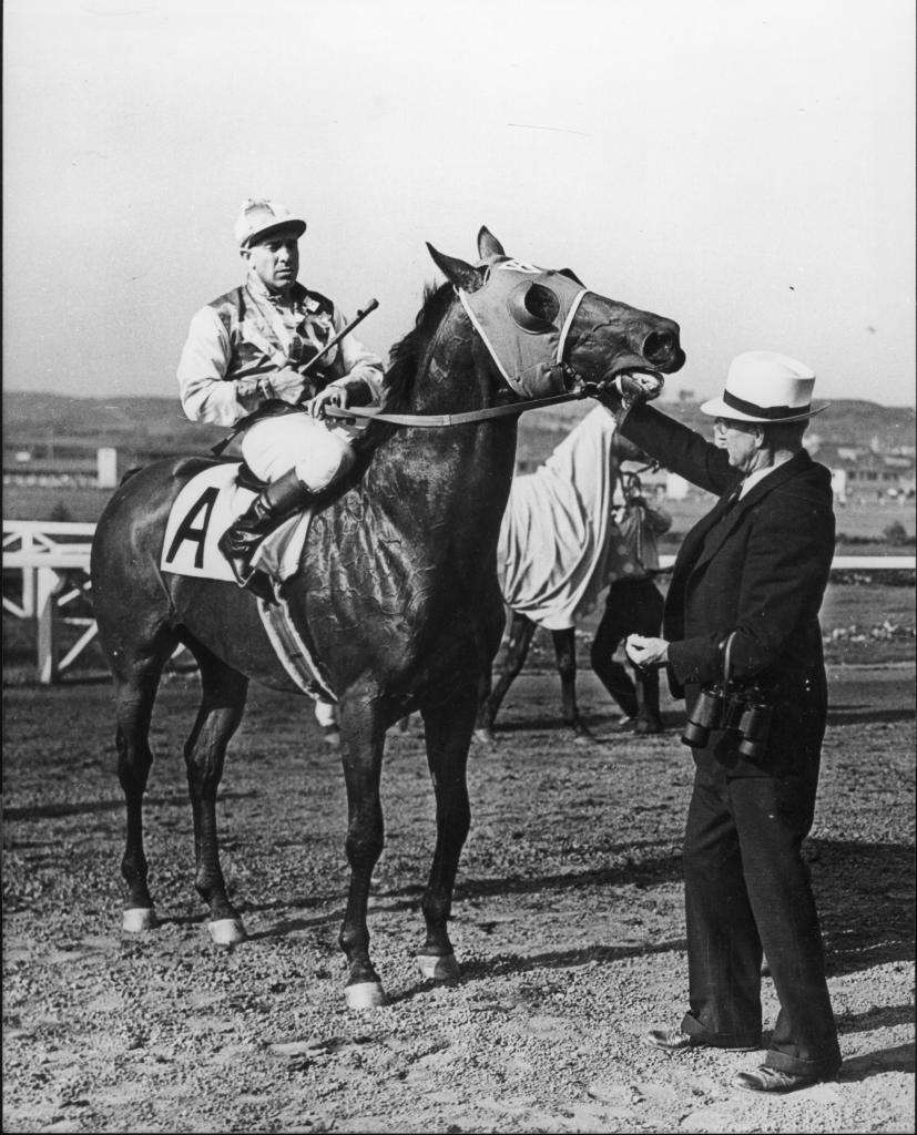 Seabiscuit returns after a match race victory over Ligaroti in 1938 at Del Mar. Jockey George Woolf and trainer Tom Smith are with the legendary horse.