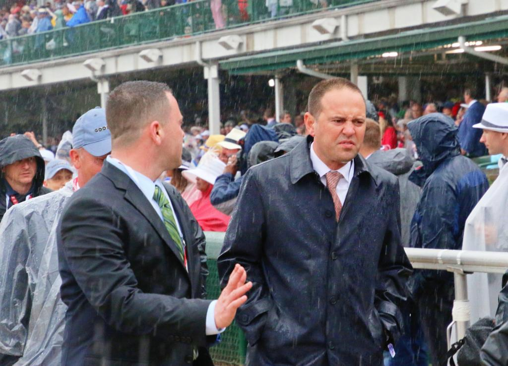 Trainer Chad Brown not enjoying the rain during the walkover. (Julie June Stewart photo)