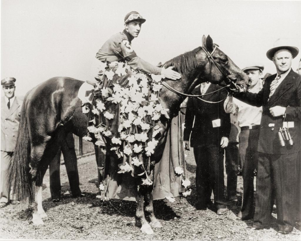 Jockey Eddie Arcaro with Whirlaway in the 1941 Belmont Stakes winner's circle. (BloodHorse Library)
