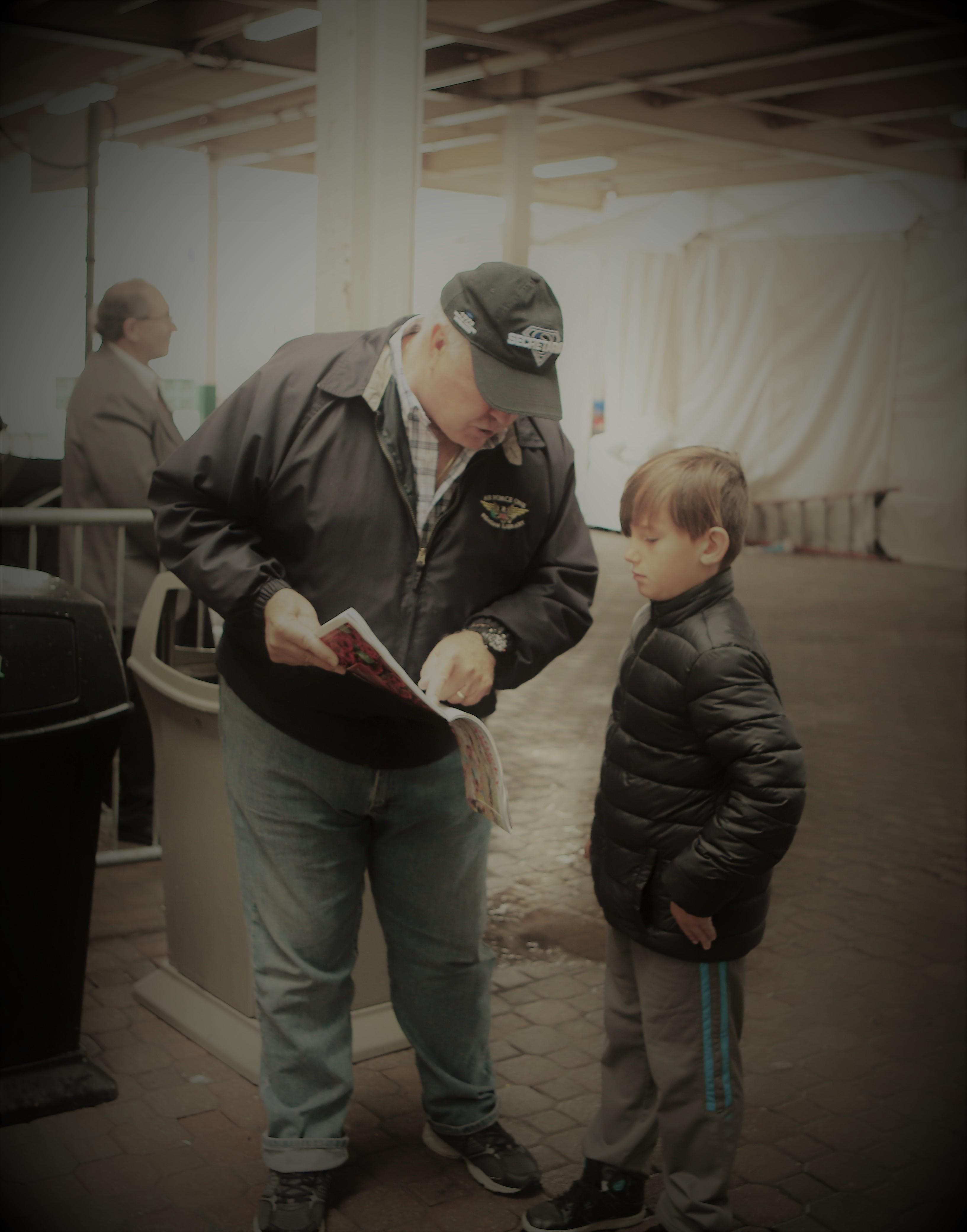 A boy learns to read a program on Oaks day