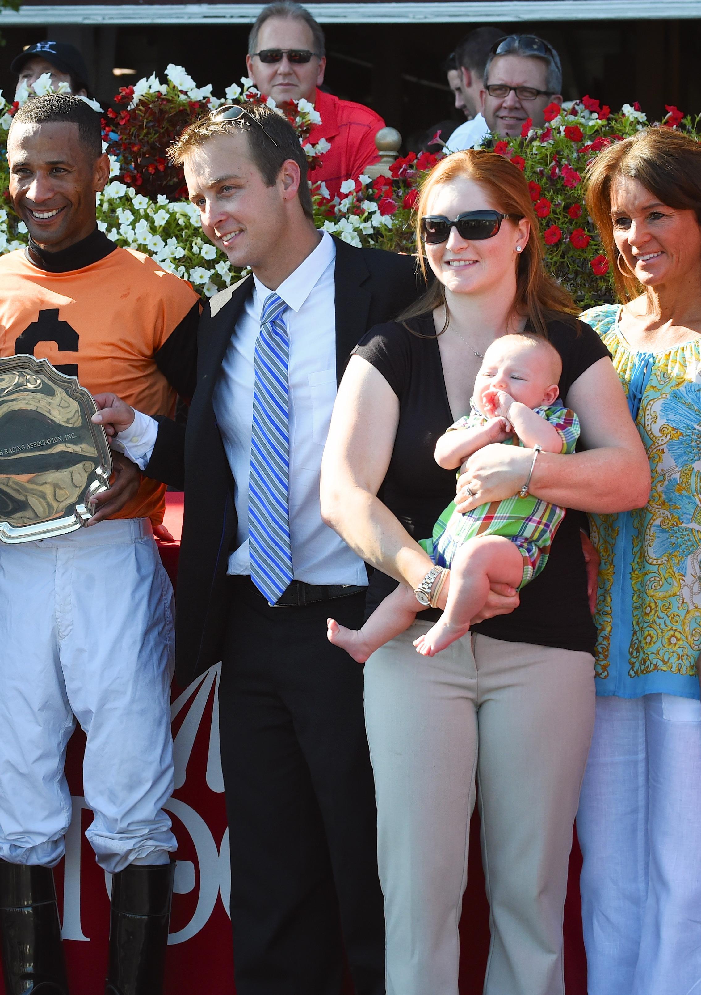 Rosie Napravnik, husband Joe Sharp, and son Carson in the Saratoga winner's circle.