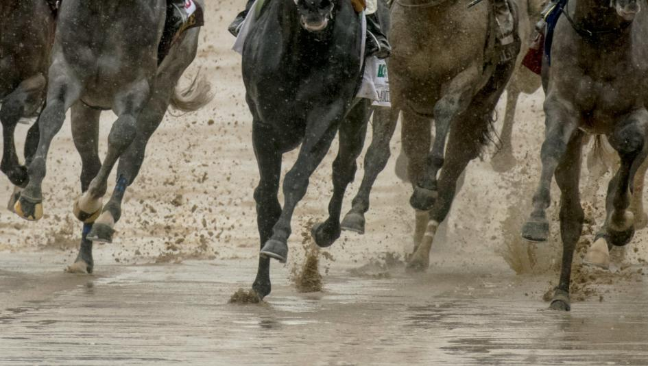 Horses race through the mud at Churchill Downs on Derby day 2018.