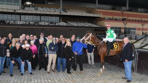 Alex Zacney (front row, fourth from right) poses with Maximus Mischief in the Remsen Stakes winner's circle.